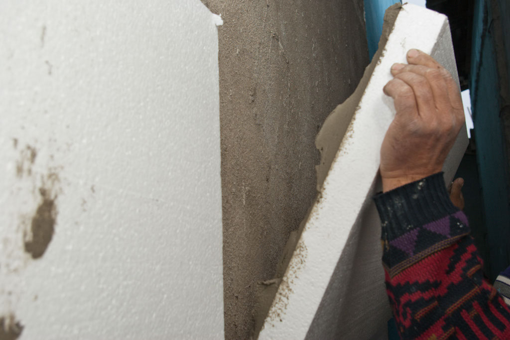 Attaching the polystyrene sheet to wall