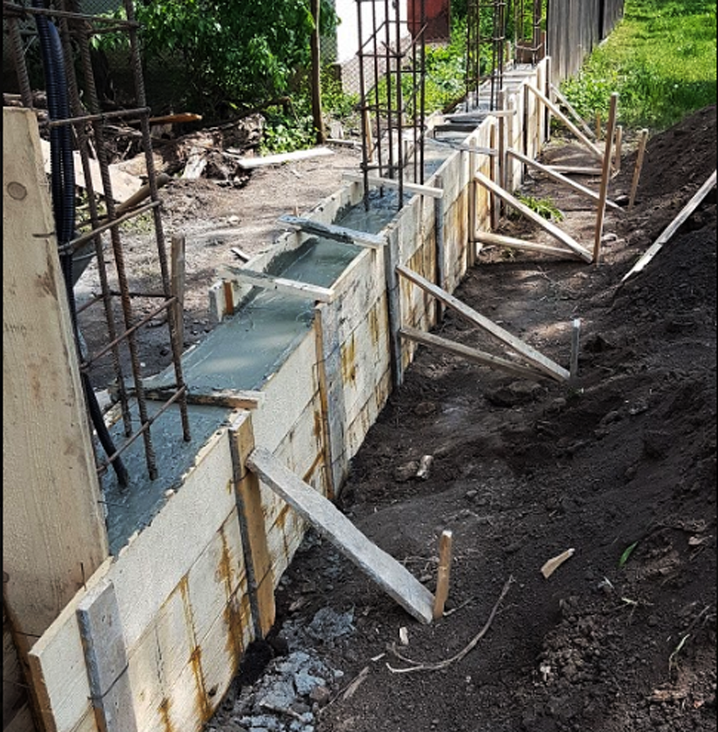 Pouring-the-concrete-in-the-base-of-the-fence
